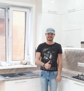 дизайнер мебели на фоне белой кухни